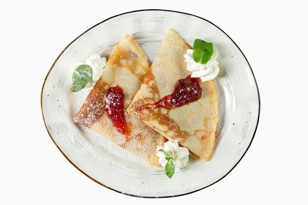 Panquecas com calda e sorvete em um prato. sobremesa apetitosa. vista do topo. isolado sobre o branco