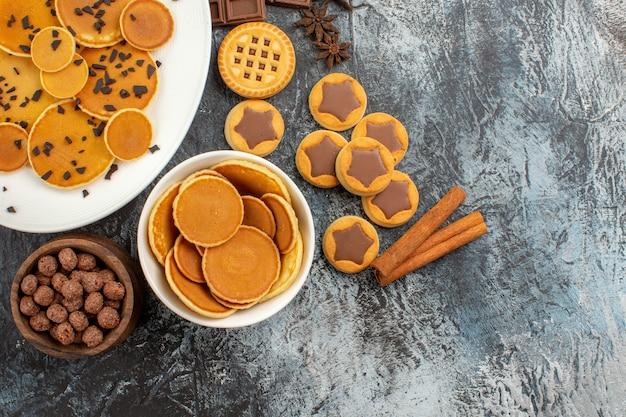 Panquecas com cereais e biscoitos com canela em fundo cinza