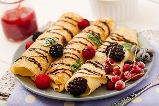 Panquecas com chocolate, geléia e frutas. saboroso café da manhã.