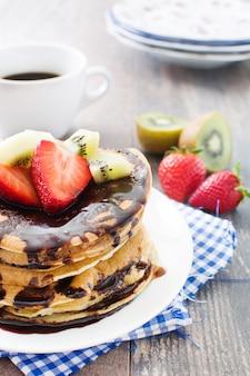 Panquecas com chocolate, morangos e kiwi na mesa de madeira