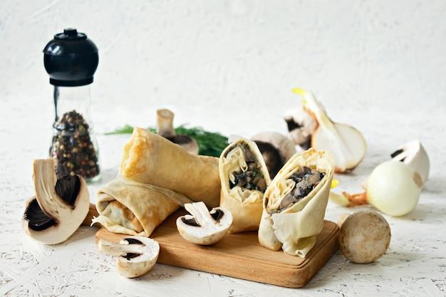 Panquecas com cogumelos em uma placa de madeira sobre um fundo branco.