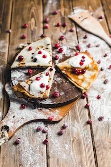 Panquecas com cranberries e creme de leite em uma placa de madeira em farinha