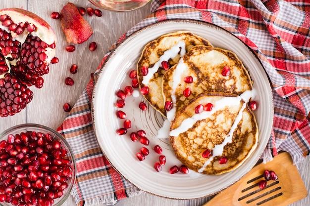 Panquecas com creme de leite e sementes de romã em uma vista superior platein