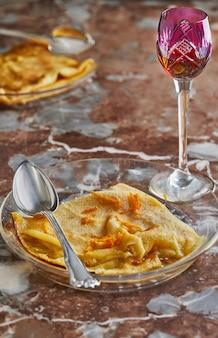 Panquecas com crepe suzette, em prato transparente com copo de licor