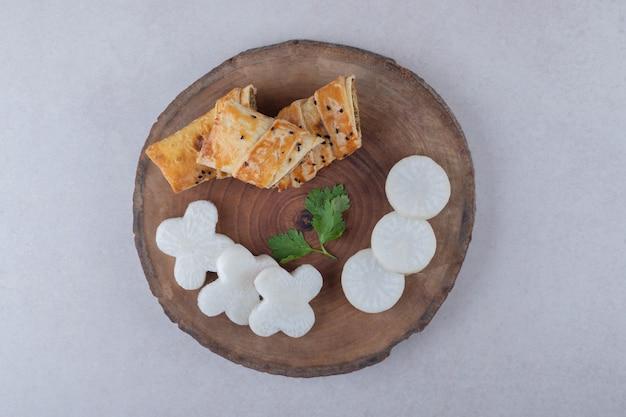 Panquecas com fatia de carne e rabanete em uma placa na mesa de mármore.