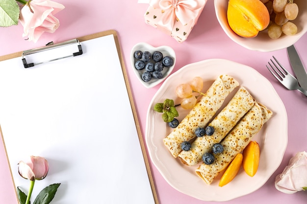 Panquecas com frutas e mel em uma mesa rosa pastel, vista superior, copie o espaço. bela porção festiva de panquecas com lugar para texto.