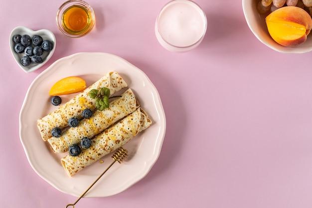 Panquecas com frutas e mel em uma mesa rosa pastel, vista superior, copie o espaço. panquecas deliciosas, panquecas finas.