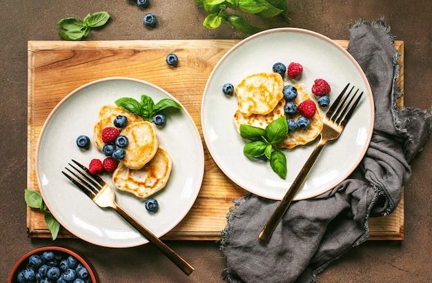 Panquecas com frutas vermelhas servidas no café da manhã, vista panorâmica em uma mesa posta