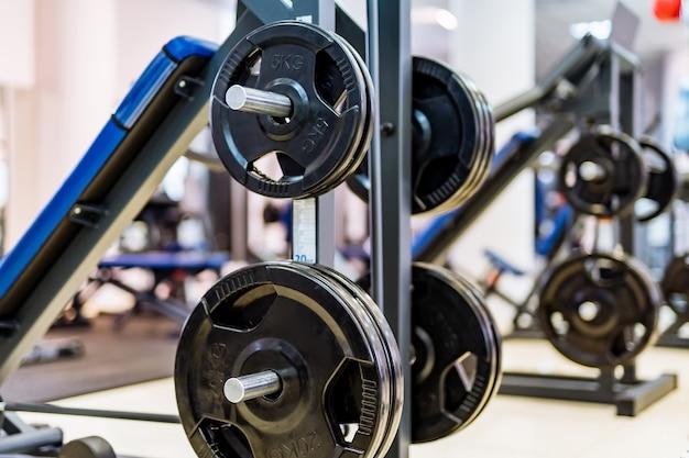 Panquecas com halteres em uma academia. esporte e conceito de vida saudável. conjunto de panquecas no fundo do ginásio. closeup de equipamento de esporte.