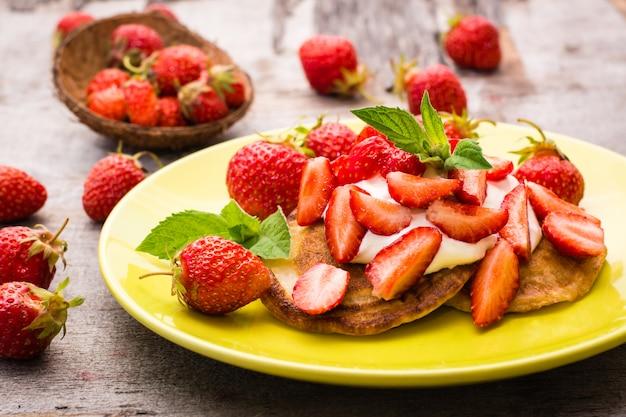 Panquecas com iogurte, morangos fatiados e folhas de hortelã em um prato