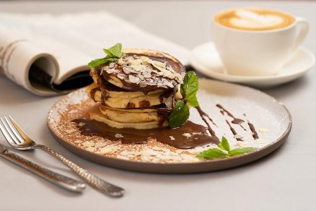 Panquecas com macarrão de chocolate e cappuccino no café da manhã.