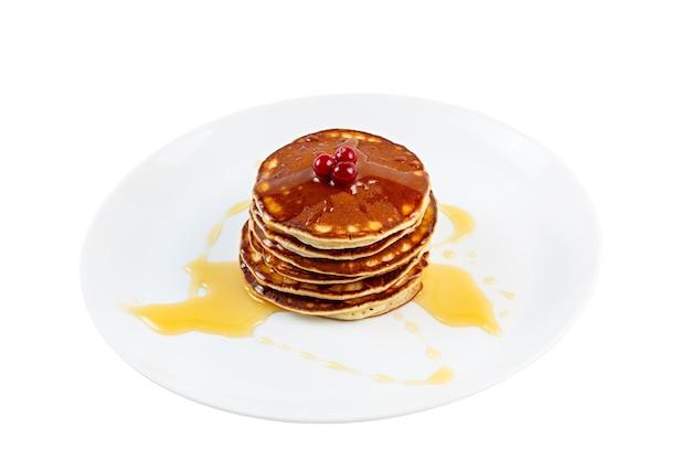 Panquecas com mel e cranberries em um prato. isolado