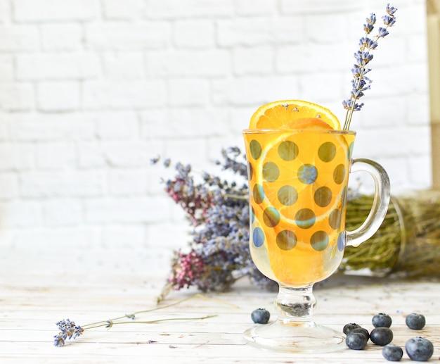 Panquecas com mirtilos folhas na limonada cítrica superior e laranja com paus de lavanda.