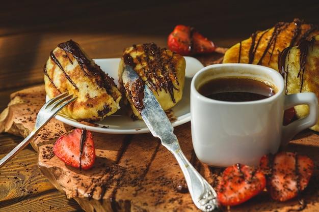 Panquecas com morangos chocolate e café em uma mesa de madeira