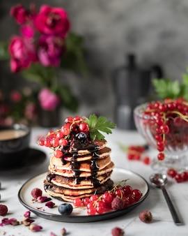 Panquecas com morangos e chocolate com um buquê de rosas vermelhas.