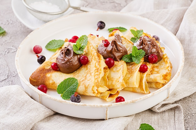 Panquecas com morangos e chocolate, decoradas com folhas de hortelã