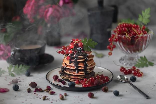 Panquecas com morangos e chocolate sobre um fundo claro com um buquê de rosas vermelhas. foto escura.