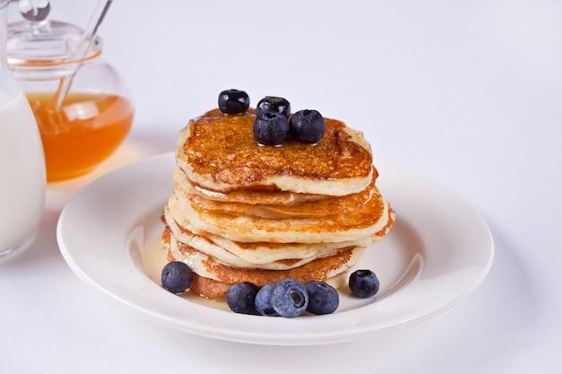 Panquecas com morangos e mel no fundo branco