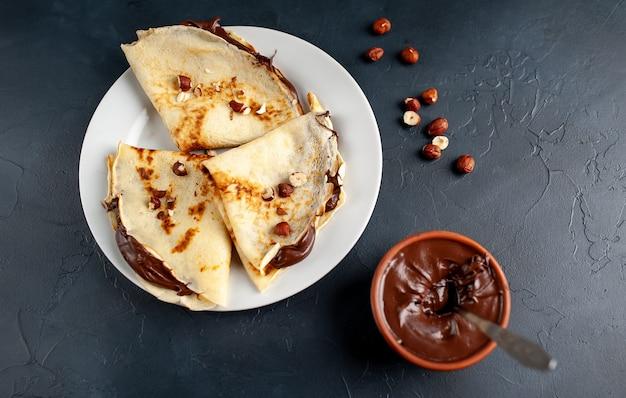 Panquecas com pasta de chocolate e avelãs, num prato branco sobre um fundo de concreto, ardósia