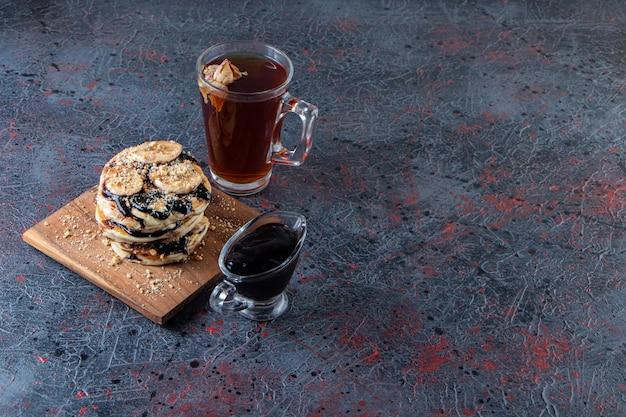 Panquecas com rodelas de banana e copo de chá quente na superfície escura.