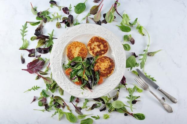 Panquecas com salada de batata em uma tigela sobre mármore