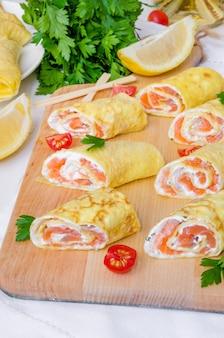 Panquecas (crepes) com salmão defumado, cream cheese e ervas em madeira branca