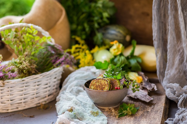 Panquecas de abobrinha em uma placa de cerâmica sobre uma mesa de madeira e colheita de outono e flores
