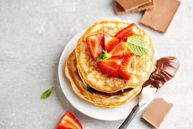 Panquecas de apetitosa saborosa e apetitosa, decoradas com pasta de morango e chocolate servidas no café da manhã. fechar-se