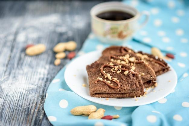 Panquecas de aveia de chocolate com caramelo e nozes na mesa de madeira cinza.