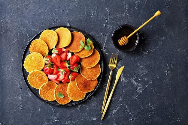 Panquecas de aveia sem glúten com morangos e mel em uma placa preta sobre uma mesa de concreto, comida saudável