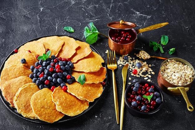 Panquecas de aveia servidas com mirtilos frescos e cranberries em uma travessa preta, ingredientes, garfo e faca dourados, molho de cranberries