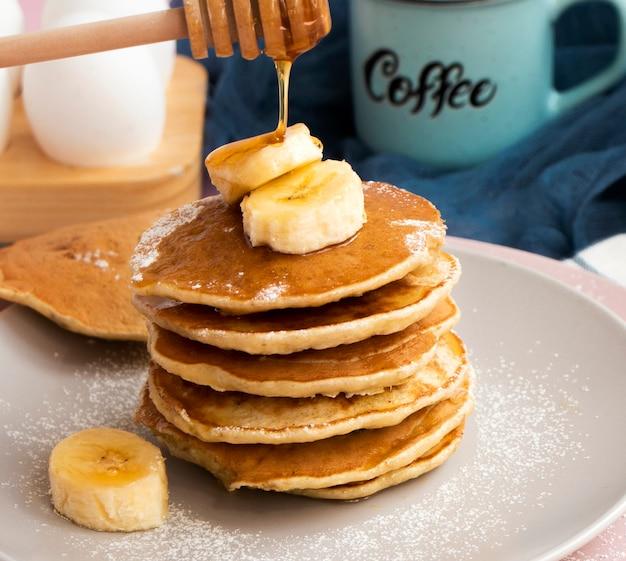 Panquecas de banana caseiras no prato polvilhado com pó e mel. panqueca com cobertura de mel