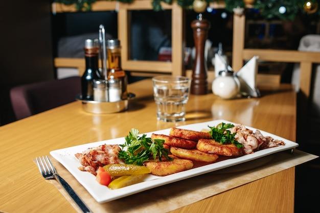 Panquecas de batata com bacon em um prato retangular branco sobre uma mesa em um restaurante.