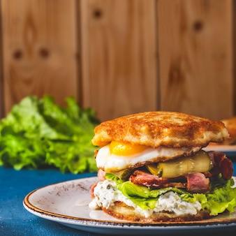Panquecas de batata deliciosa hambúrguer ovos fritos, bacon e sal pepino.
