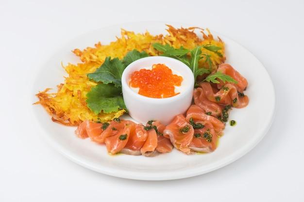 Panquecas de batata, salmão, peixe e caviar vermelho