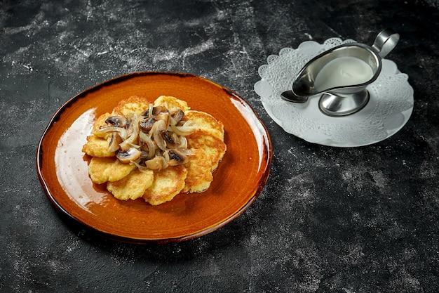 Panquecas de batata tradicionais com cogumelos da floresta e creme de leite em uma mesa escura, raggmunk, draniki, deruny