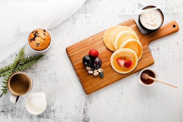 Panquecas de café da manhã vista superior em cima de madeira