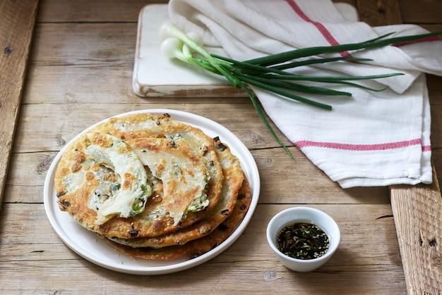 Panquecas de cebolinha apetitosas caseiras e um monte de cebolinha. estilo rústico.