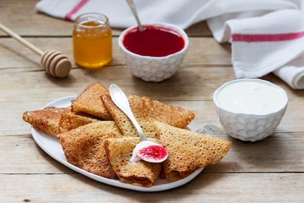 Panquecas de centeio e grãos integrais, servidas com creme de leite, mel e molho de morango. estilo rústico.