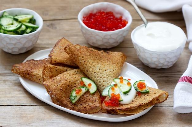 Panquecas de centeio e grãos inteiros servidos com creme de leite, caviar e pepino. estilo rústico.