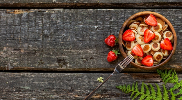 Panquecas de cereal de panqueca minúscula mini em uma tigela de madeira com morangos em um fundo de madeira. vista do topo. copie o espaço