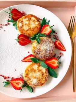 Panquecas de cheesecakes caseiras com morangos em um prato branco e garfo de ouro em uma bandeja rosa claro