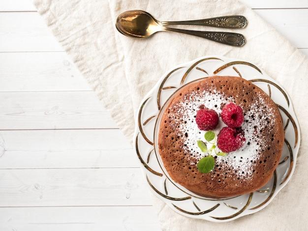 Panquecas de chocolate com framboesa de açúcar em pó na luz de fundo