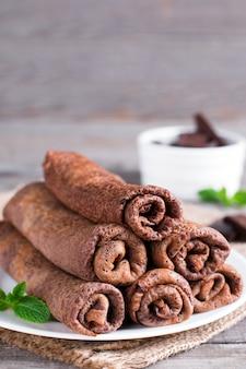 Panquecas de chocolate enroladas em um prato sobre um fundo de madeira