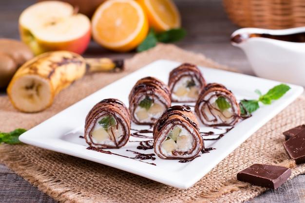 Panquecas de chocolate finas enroladas em um prato sobre um fundo de madeira