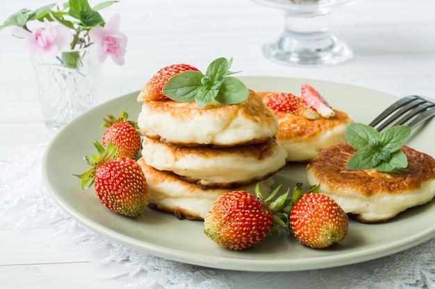 Panquecas de coalhada com morangos e hortelã em um prato.