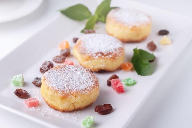 Panquecas de coalhada com passas e frutas cristalizadas em um prato branco vista superior