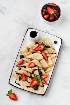 Panquecas de crepes caseiras com calda de chocolate, morango fresco e mel no café da manhã em lindo prato de cerâmica branca. espaço para texto ou receita. vista do topo