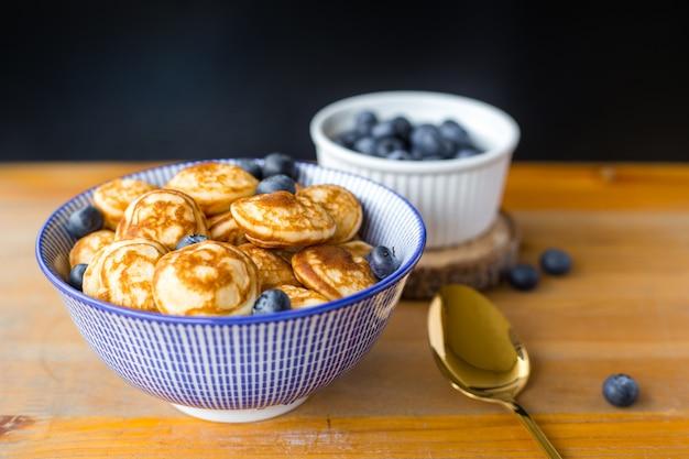 Panquecas de mini cereal com frutas e colher na mesa de madeira