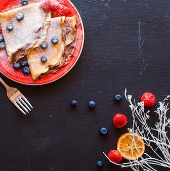 Panquecas de morangos frescos ou crepes com morangos e chocolate
